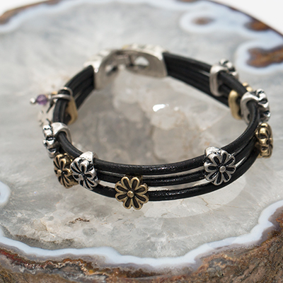 "LUCKY BRAND<sup>&reg;</sup> Daisy Leather Bracelet - This bracelet features three rows of leather strands accented with antiqued gold and silver-toned flower charms.  Bracelet has silver-toned closure and measures 7.5""L."